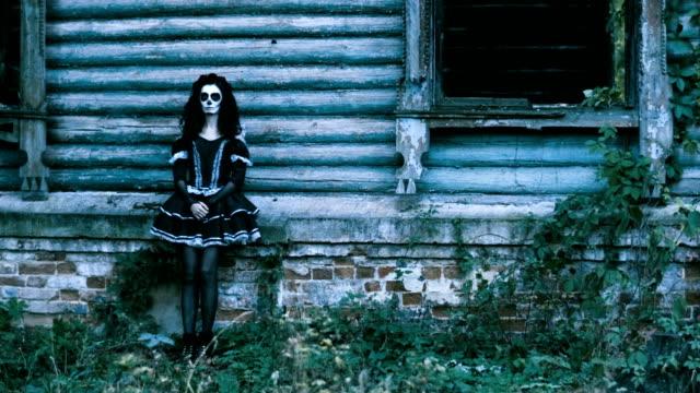 Die-Frau-mit-Halloween-Make-up-in-schwarzer-Kleidung-steht-vor-dem-Haus-4K