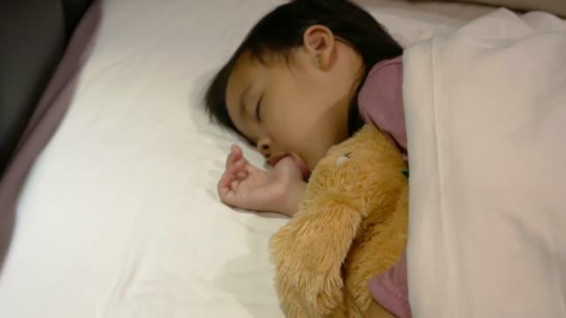 Asiatische-Mutter-legt-Decke-auf-ihre-Tochter-die-im-Bett-schläft-und-Gute-Nacht-Kuss-mit-Liebe-Gesundheitskonzept-