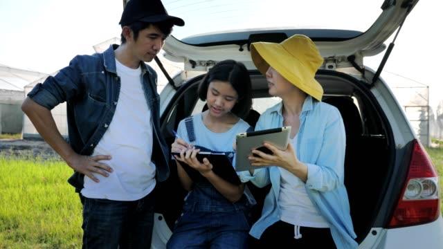 Familia-asiática-inteligente-sentada-en-el-coche-y-el-uso-de-la-tableta-digital-para-el-acceso-a-Internet-frente-a-la-casa-verde-concepto-de-agricultura-inteligente