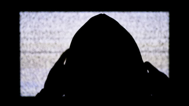Silhouette-of-Man-s-Head-in-Hood-is-Watching-White-Static-Noise-and-TV-Interference