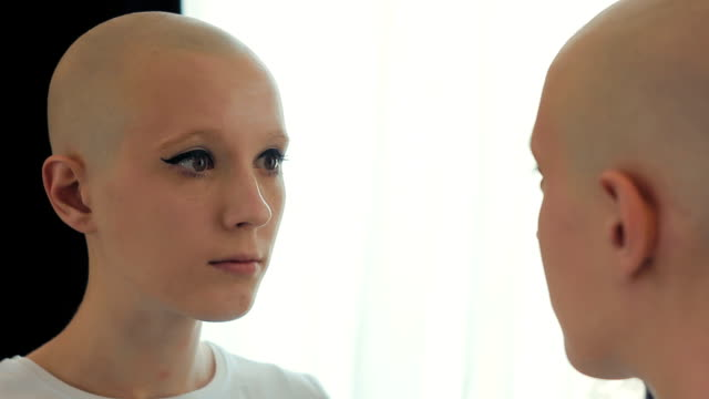 Sad-woman-suffering-from-cancer-looking-at-herself-in-the-mirror