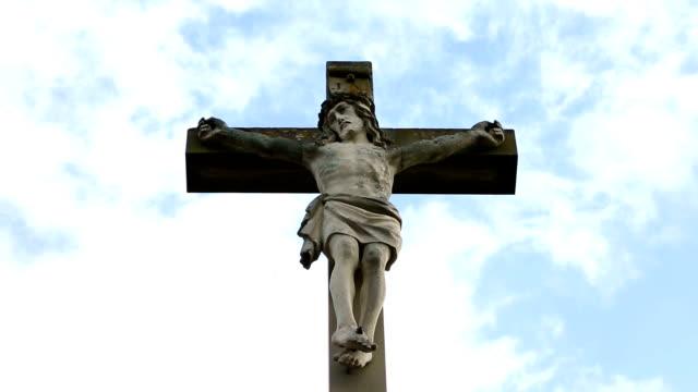 Nahaufnahme-des-steinernen-Kreuz-mit-Jesus-und-blauer-Himmel-mit-Wolken
