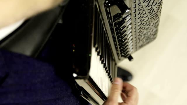 Primer-plano-de-la-mano-de-derecha-de-un-hombre-tocando-un-acordeón-negro-