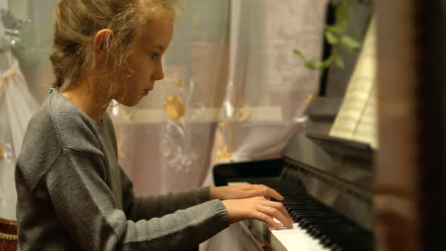 Pretty-little-girl-learns-to-play-the-piano-