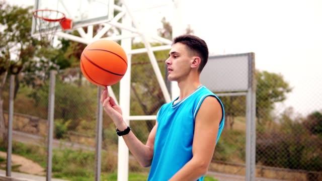 Retrato-de-un-jugador-de-baloncesto-que-hace-girar-una-pelota-de-baloncesto-en-el-patio-de-la-calle-Tiro-de-cámara-lenta