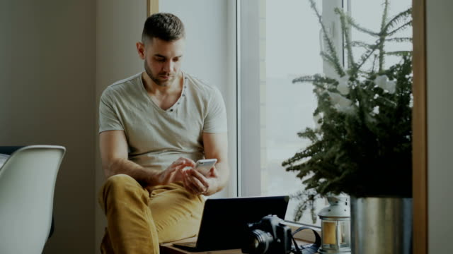Hombre-joven-atractivo-navegación-teléfono-smartphone-sentado-en-el-alféizar-de-la-ventana-con-ordenador-portátil-y-cámara-en-café
