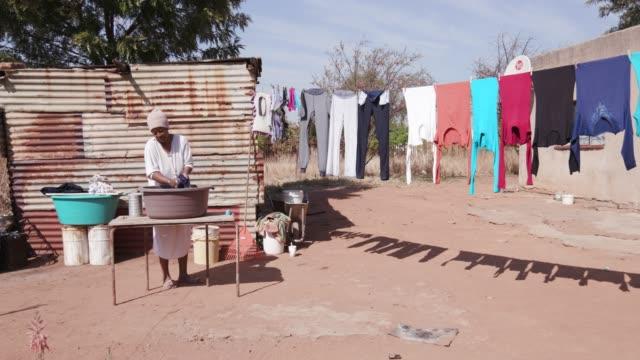 Mujer-africana-sin-agua-lavando-la-ropa-en-un-cubo-delante-de-su-choza-de-lata-casera