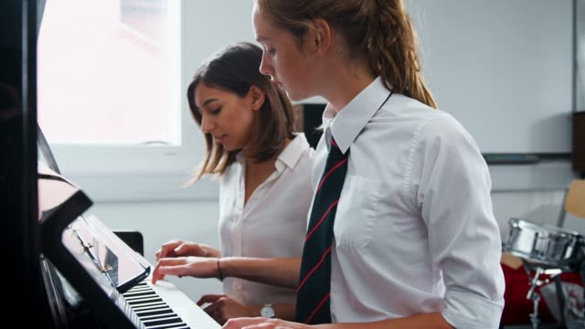 Female-Pupil-With-Teacher-Playing-Piano-In-Music-Lesson