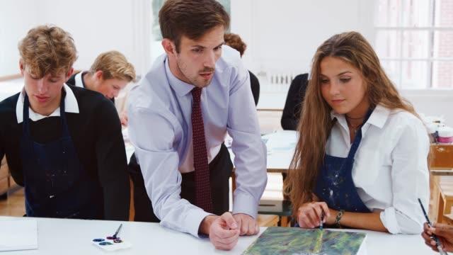 Männliche-Lehrer-helfen-Jugendliche-Schülern-im-Kunstunterricht