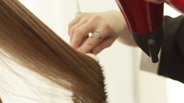 Hairstylist-using-dryer-for-drying-long-hair-and-hairbrush-for-styling-after-hairdressing-in-beauty-studio-Close-up-hairdresser-making-hairstyling-in-hairdressing-salon