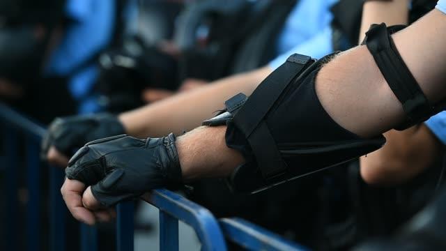 Oficial-de-policía-de-las-manos-en-una-valla-de-seguridad-durante-un-motín