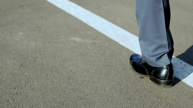 Closeup-of-male-legs-walking-along-arrow-startup-path-of-ambitious-leader