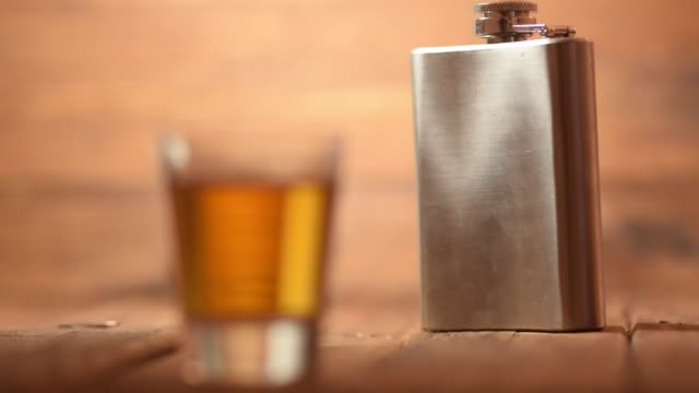 Focus-pull-of-a-whiskey-shot-glass-to-a-metal-hip-flask-in-the-background