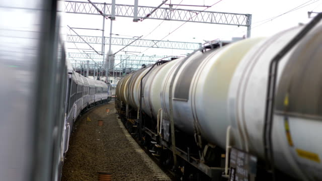Passanger-train-moving-next-to-cisterns-on-railway-track-in-4k-slow-motion-60fps