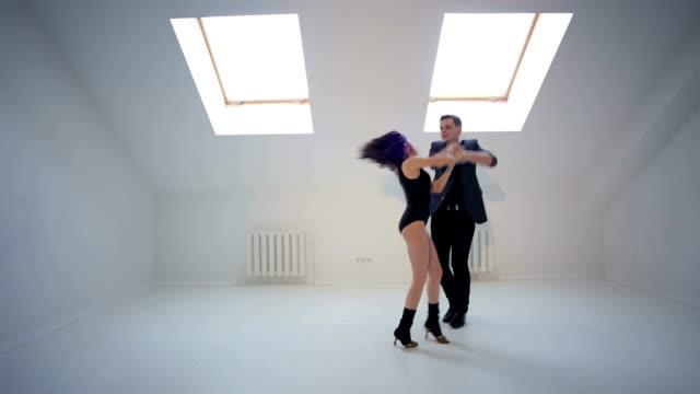 Joven-pareja-bailando-la-salsa-o-la-bachata-en-la-sala-de-baile-