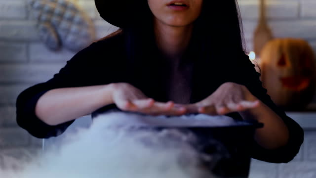 Scary-witch-making-magic-potions-in-her-pot-with-white-smoke-Halloween-eve