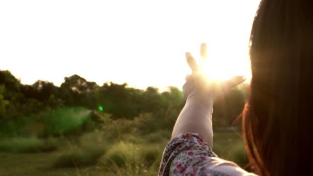 Sonnenlicht-durch-weibliche-Hände-während-ihr-Blick-auf-Sonne