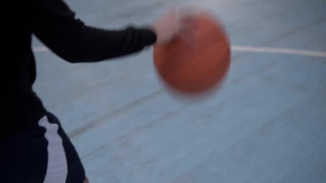 Weibliche-Basketballspielerin-training-Basketball-spielen-Basketball-Spieler-Prellen-des-Balls-Slow-Motion-Aufnahme-des-Basketball-Spieler-auf-dem-Platz-im-freien-training