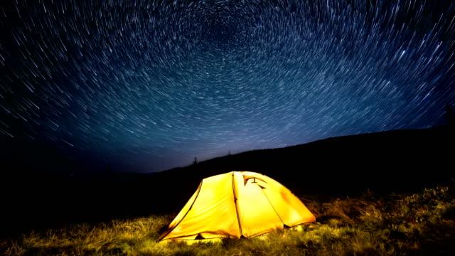 Time-lapse-Círculos-de-estrella-por-encima-de-las-montañas-de-noche-y-una-tienda-de-campaña-que-brilla-intensamente