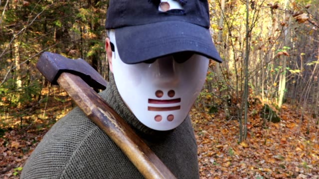 Man-in-Halloween-mask-with-an-ax-on-the-shoulder-in-close-up