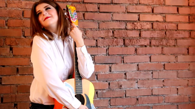 Girl-in-white-shirt-posing-with-a-guitar-in-hippie-style-