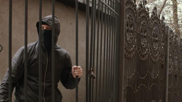 Bandit-man-in-black-mask-and-hood-with-baseball-bat-crawls-through-fence-mesh