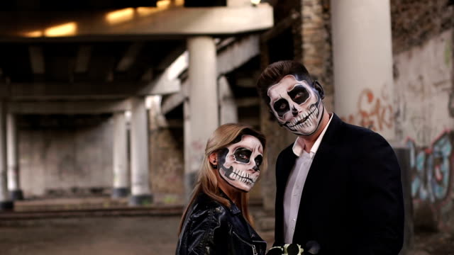 Halloween-loving-couple-in-costumes-of-skeletons-and-sugar-skull-make-up-