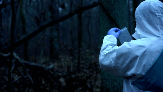Forensic-science-expert-collecting-and-preserving-evidence-at-murder-site