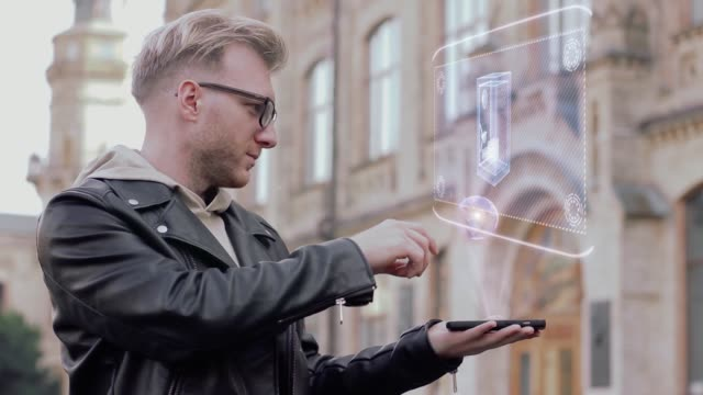Smart-young-man-with-glasses-shows-a-conceptual-hologram-safe-with-money