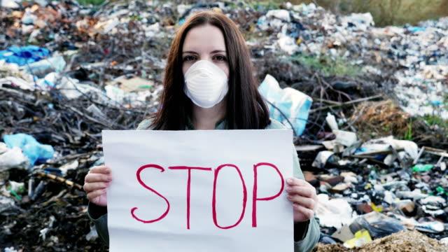 Activista-con-el-cartel-de-la-parada-en-basurero