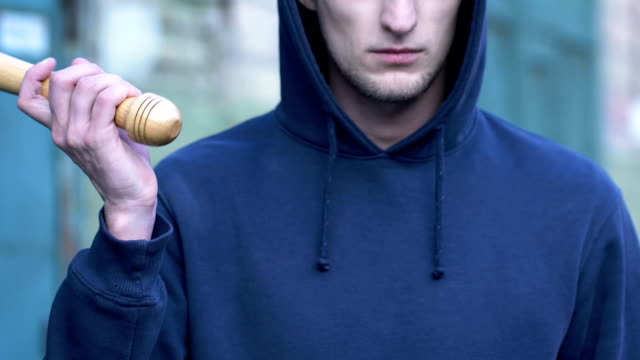 Aggressive-man-holding-baseball-bat-ready-to-attack-street-groupings-of-bully