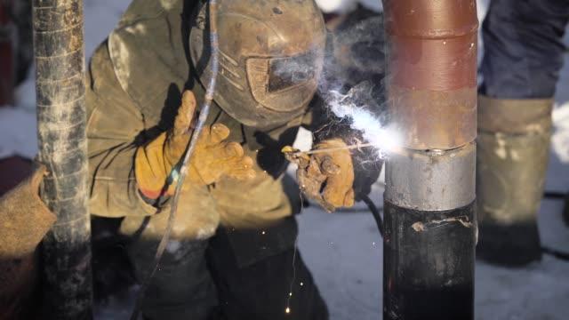Trabajador-produce-la-soldadura-de-la-pipa-en-la-calle-En-invierno-temperaturas-bajas-es-difícil-montar-el-cable-de-la-pipa