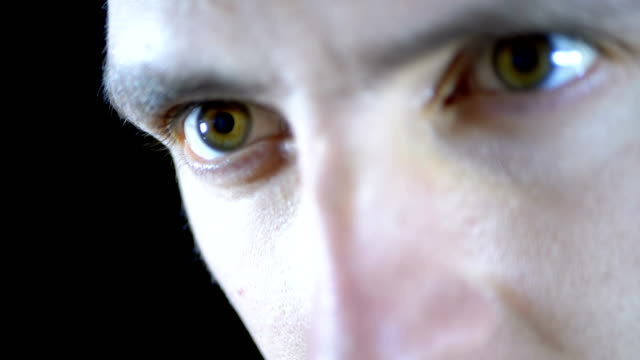 Close-up-of-the-eyes-and-face-of-a-young-man-working-at-a-computer-on-a-Black-Background