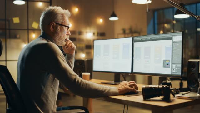 El-diseñador-creativo-de-software-móvil-de-mediana-edad-sentado-en-su-escritorio-utiliza-un-ordenador-de-sobremesa-con-dos-pantallas-que-muestran-el-proceso-de-diseño-de-aplicaciones-de-smartphone-Elegante-oficina-de-estudio-moderno