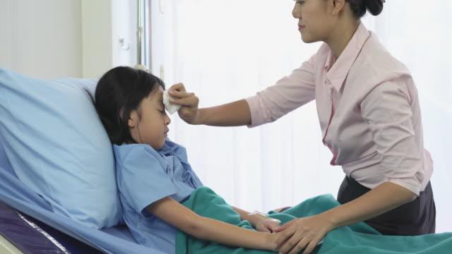 Madre-asiática-frotar-la-niña-paciente-del-cuerpo-para-reducir-la-temperatura-y-el-examen-físico-en-el-hospital-Concepto-de-familia-medicina-salud-y-tecnología-