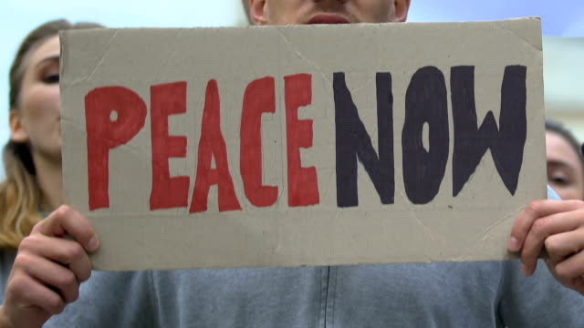 Manifestantes-con-pancartas-gritando-Paz-ahora-movimiento-anti-guerra-contra-el-terrorismo