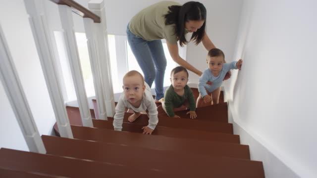 Asiático-bebé-trillizos-y-mamá-en-escalera