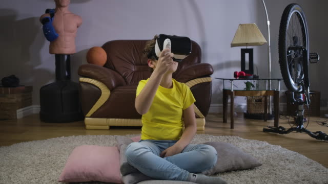 Male-Caucasian-teen-wearing-VR-headset-using-remote-control-to-play-the-game-Child-looking-around-and-smiling-Augmented-reality-VR-googles-Cinema-4k-ProRes-HQ-