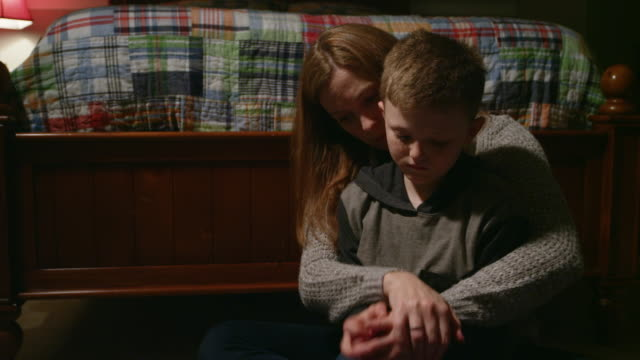 A-mother-with-her-arms-around-her-young-son-who-looks-sad