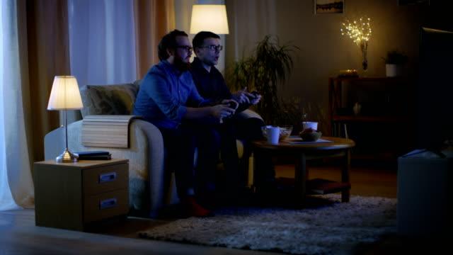 En-la-noche-dos-amigos-están-sentados-en-un-sofá-en-la-sala-de-estar-y-jugando-juegos-de-video-competitivos-Uno-de-ellos-gana-y-está-disfrutando-de-su-éxito-