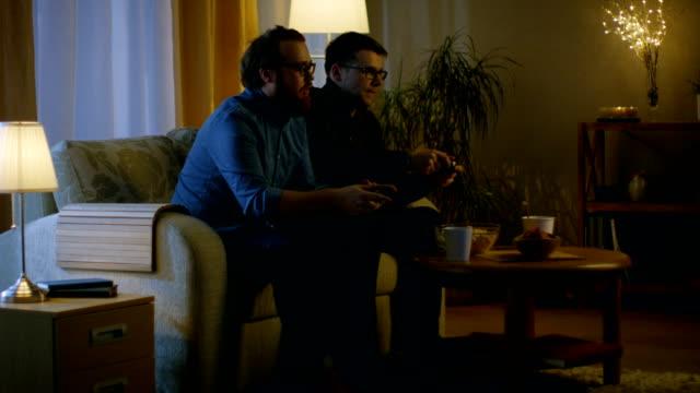 En-la-noche-dos-amigos-están-sentados-en-un-sofá-en-la-sala-de-estar-y-jugando-juegos-de-video-competitivos-