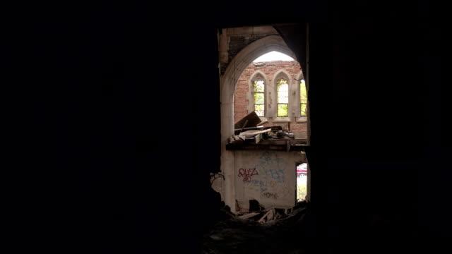 POV:-Verfallene-alte-gotische-Kathedrale-gesehen-durch-ein-Loch-in-einer-verfallenen-Mauer