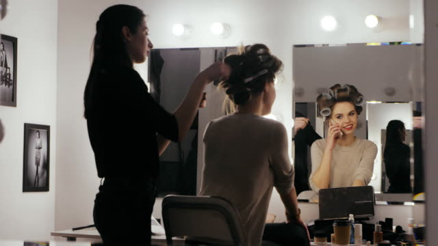 Woman-with-hair-curlers-calling-by-mobile-phone-front-mirror-in-dressing-room