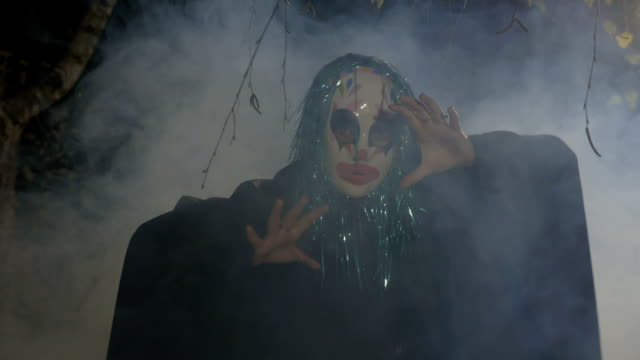 Maléfico-payaso-divertido-de-halloween-usando-una-máscara-y-verde-pelo-falso-realizando-un-baile-mal-en-un-bosque-oscuro