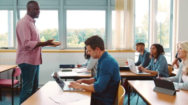 Tutor-masculino-permanente-dar-clase-de-estudiantes-maduros