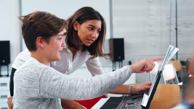 Männliche-Schüler-mit-Lehrer-im-Musikunterricht-Klavier-zu-spielen