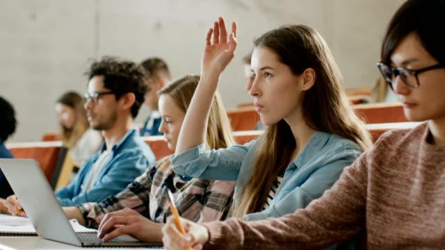 Hermosa-joven-estudiante-utiliza-Laptop-escuchando-una-conferencia-en-la-Universidad-ella-levanta-mano-y-profesor-pide-una-pregunta-Multi-étnico-grupo-de-estudiantes-brillantes-moderno-