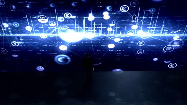 Businessman-approaches-a-wall-of-financial-data-