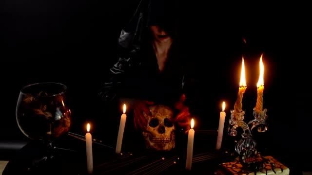 Con-las-manos-de-sangre-sosteniendo-el-cráneo-de-la-bruja