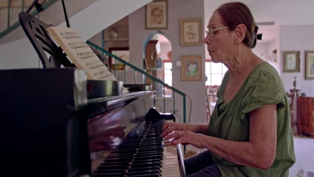 Old-woman-playing-a-grand-piano-at-her-home